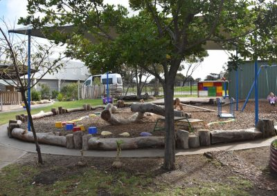 play yard with toddler on the swings on the right